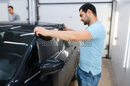 male worker tries on wetted car