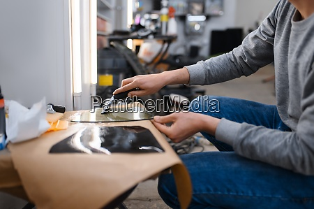 male worker prepares sheet of car