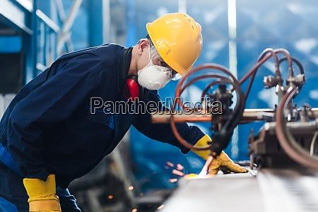 asian worker using cnc plasma cutter