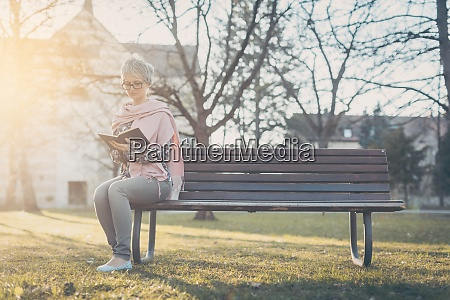 senior woman sitting alone on bench