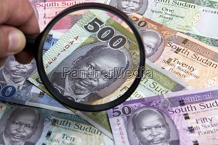 south sudan money in a magnifying