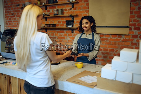 male barista in cafe customer pays