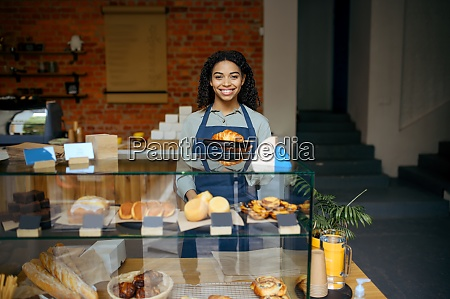 female barista holds plate with croissant