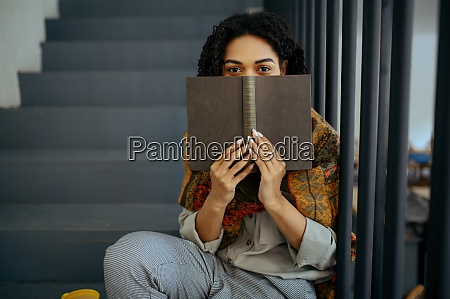 female student with book sitting on
