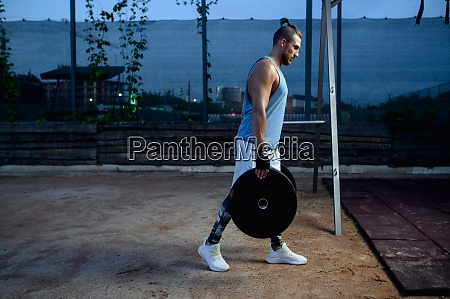 man carries barbell weights street workout