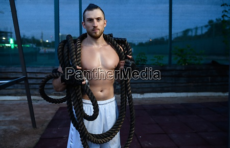 man poses with crossfit ropes street