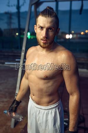 tired muscular man sweats street workout