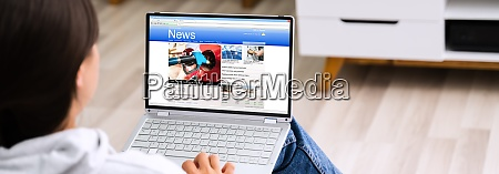 watching news on laptop computer screen
