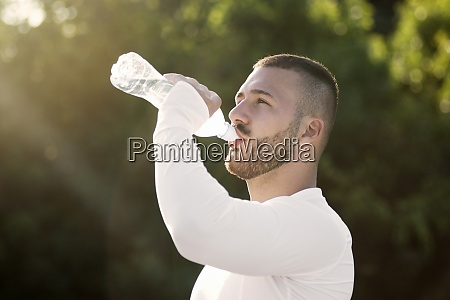 young guy drinking water from bottle