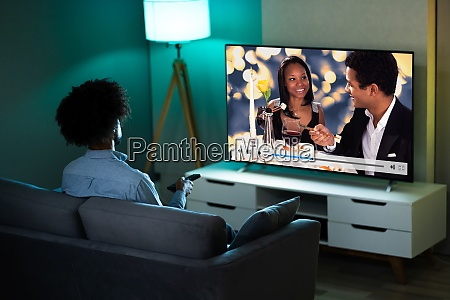 african man watching tv movie