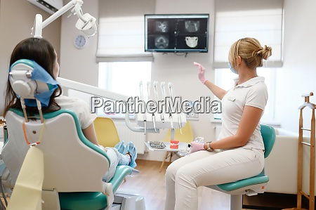 female dentist shows to patient x