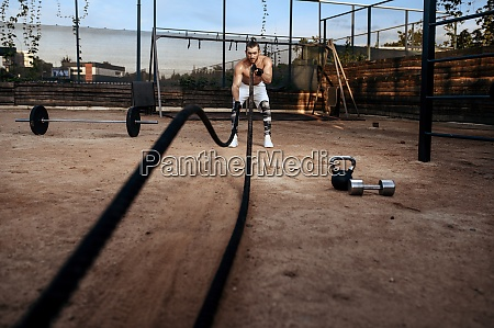 man doing exercise with ropes workout