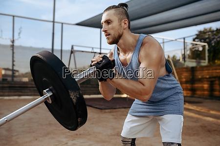 man prepares barbell weights street workout
