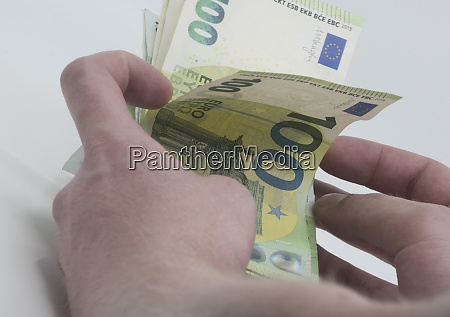 holding one hundred euro bills in