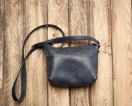 blue leather bag on gray wooden