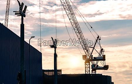 silhouette construction crane against sunset sky