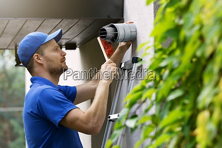 hvac service worker doing maintenance and
