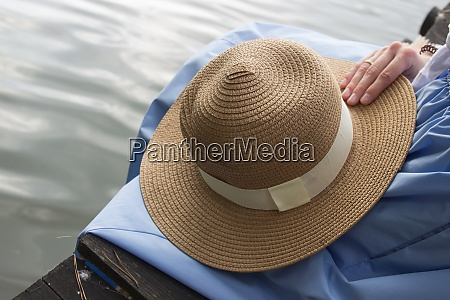 womens straw hat hold in hand