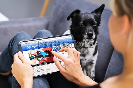 reading online newspaper on tablet watching