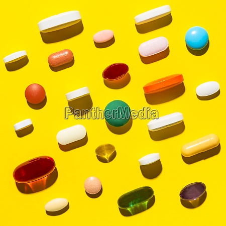 pills and capsules on yellow