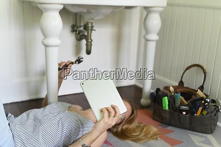 woman repairing sink while watching diy