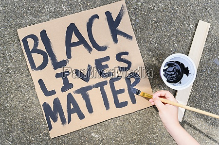 womans hand painting black lives matter