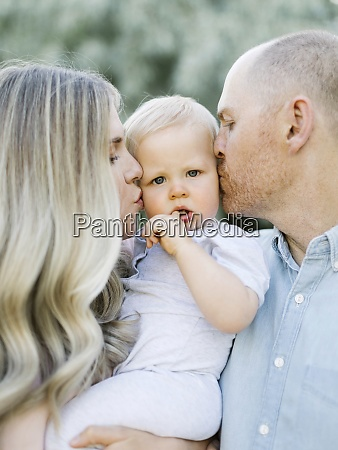 parents kissing baby boy son