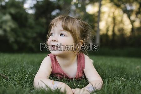 girl 2 3 lying on grass