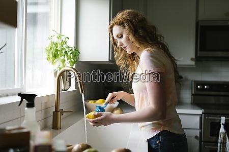 woman washing lemon with brush