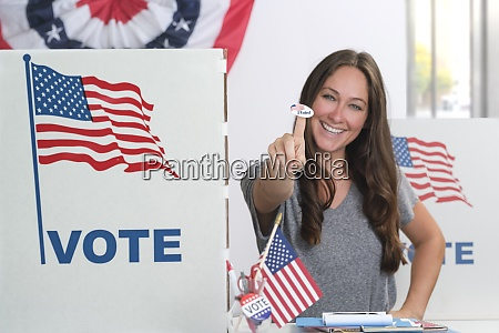 woman holding voting sticker