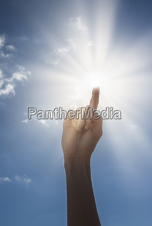 womans hand pointing towards sun