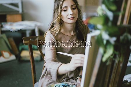 woman painting on canvas in art