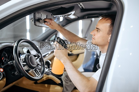 worker with spray moisturizes car interior