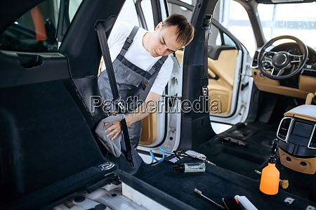 worker with rag wipes car interior