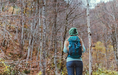woman hiking the autumn woods