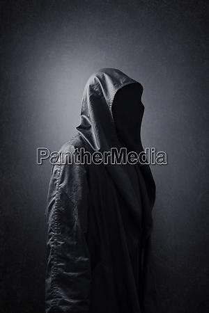 scary figure in hooded cloak in