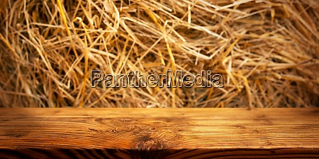 wooden table with straw background