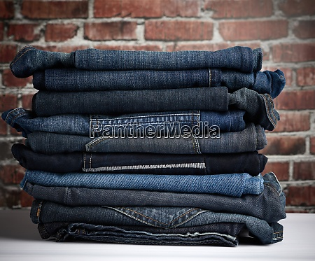 pile of folded blue jeans different