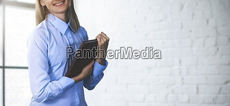 smiling woman manager holding tablet and