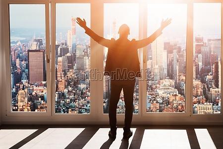 african businessman raising hands rear view