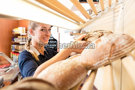 bakery woman putting bread in shop