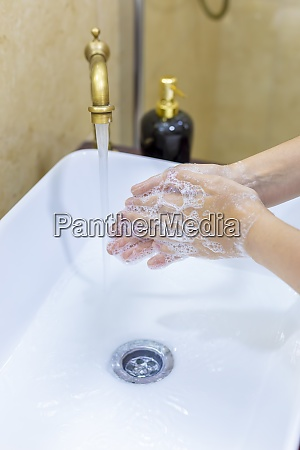 woman washing and disinfecting hands with