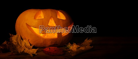 glowing carved halloween pumpkin with autumn