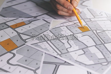 hand with pencil on cadastral map