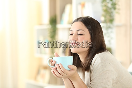 satisfied woman relaxing holding coffee mug