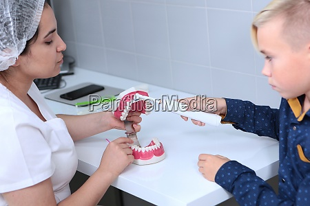 dentist teaches a boy to brush