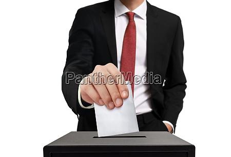 man casting his vote into ballot