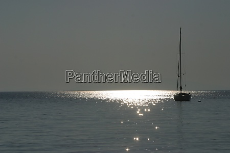 boat sailing away at sundown