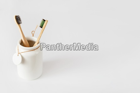 ceramic cup with wooden toothbrushes on