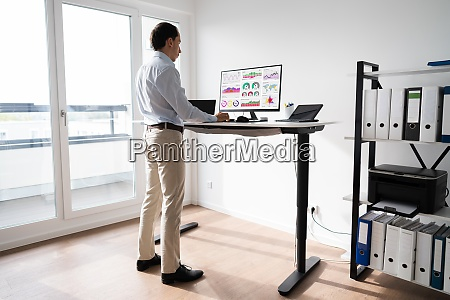 man working on computer at standing